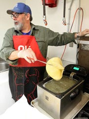 Youth minister Norm Georgina flash fries some corn tortillas Wednesday during the 20th annual Cheese Enchilada Take-Out fundraiser in the kitchen at the St. Mary's Parish Center in Farmington.