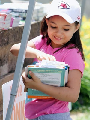 Savanna Garza, 7, smiles while looking at the books that she picked out herself and her sister, Delia, 9, Wednesday at North Hill Elementary School. The books were being distributed by the Burlington Rotary Club which promotes reading and literacy among school children. The club was distributing the books along with books donated by the Burlington Public Library in conjunction with school meal pick ups.