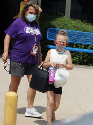 Makenna Rogers, 7, a summer school student at North Hill Elementary School, is escorted by her teacher, Kim Scherk, July 7 as she makes her way to a waiting vehicle at the end of the school day at the Burlington elementary school. North Hill Elementary School's in-person summer program was abruptly suspended just one week and two days after it started after eight students had temperatures of 100.4 degrees or higher over a two-day period. Students who had high temperatures were checked again after sitting in an air-conditioned vestibule.