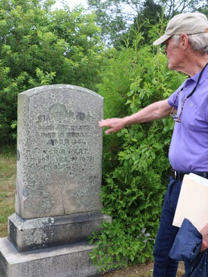 Hillside Cemetery manager Bob Martin talks about one of the headstones in the historical cemetery.