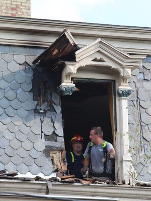Firefighters assess damage after putting out a fire in a rooming house at 204 Main St. in Spencer on Monday.