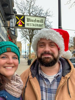 Nicole and Eric Dykstra of Holland pose for a photo in front of Windmill Restaurant on Eighth Street. Following the recent order shutting down dine-in service, the couple decided to forego traditional Christmas presents to support local restaurants via carryout.