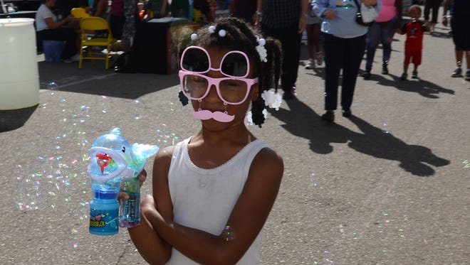 A young lady tries to entice passers-by to purchase a bubble machine during the Sept. 2 state fair in Novi.