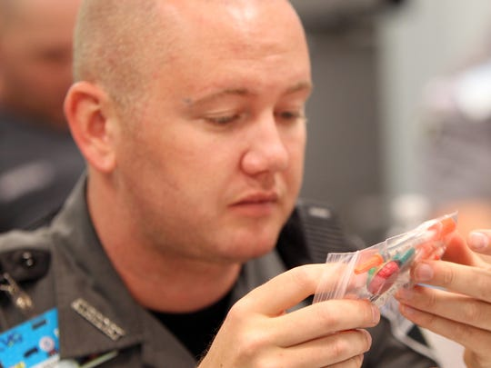 "Cincinnati/Northern Kentucky International Airport Police officer Jason Gilliam looks over a sample ""cooker kit"" used by drug addicts during a demonstration of naloxone."