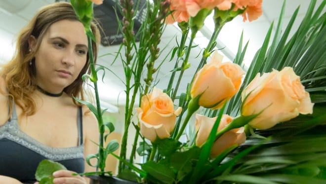 New Mexico State University student Hanah Rheay, 23, looks over her flowers before practicing her arrangement on Thursday, July 27, 2017, at Skeen Hall on campus. The floral students are practicing for an upcoming floral design competition at the Two Weddings and a Funeral floral convention Aug. 4-6 at the New Mexico Farm and Ranch Heritage Museum.