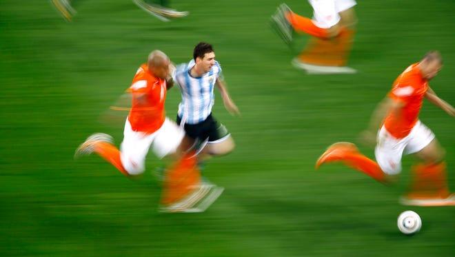 Argentina's Lionel Messi fights for the ball with the Netherlands on Wednesday. When Argentina takes on Germany Sunday, it looks like a meeting between individual scoring talent and the tight discipline of a collective unit.
