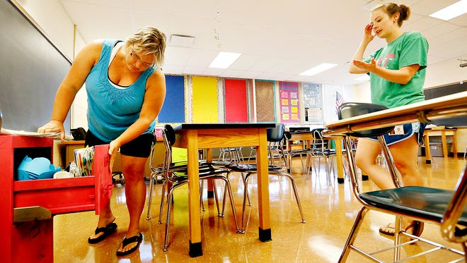 Eighth-grade learning support teacher Lynda Shearer, left, examines a file cabinet painted by eighth-grade pre-algebra teacher Lauren Nolan as the teachers get their classrooms ready for the new school year at Dover Area Intermediate School in Dover, Thursday, Aug. 4, 2016. Dawn J. Sagert photo