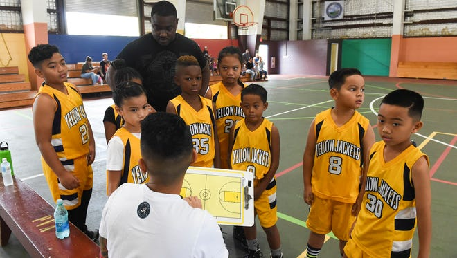 In this Aug. 4 file photo, Yellowjackets Yellow players huddle around their coach for a play during a Guam Youth Basketball Association Drug Free League Under-10 division playoff game at Astumbo Gym. The Yellowjackets Yellow won a consolation game against the Barrigada Crusaders on Aug. 7.