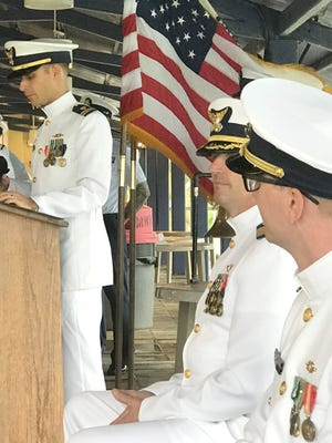 Lt. Collinson Burgwyn speaks duroing the change of command ceremony for the Coast Guard Cutter Washington at Victor Pier on Naval Base Guam. Center is Capt Christopher Chase, Commander, Coast Guard Sector Guam, and Lt. Grant Rutter, who is the new commanding officer, is on the right.