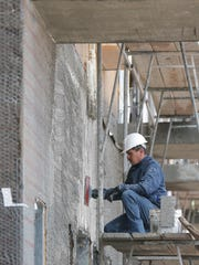 A construction worker was busy last week at the 87-unit