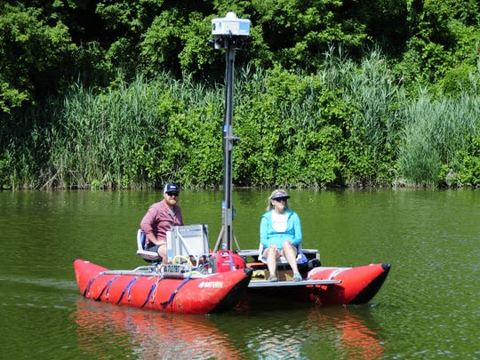 Lori Eschenburg of the St. Clair County Metropolitan Planning Commission and Ryan Abrahamsen of Terrain 360 map a portion of the Island Loop National Water Trail on the Black River. The loop recently was designated as a state water trail.