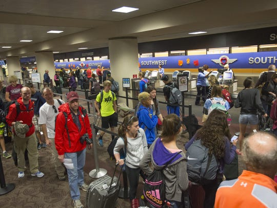 A line of travelers form outside the Southwest ticketing booths on the Sunday before Thanksgiving 2014 at Phoenix Sky Harbor International Airport.
