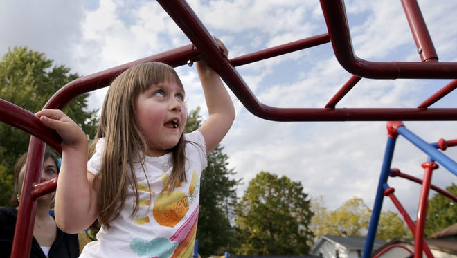Emily De Young, 7, plays at the playground outside St. Margaret Mary Elementary School Monday, Sept. 28, 2015, in Neenah, Wis. Emily has been cancer free since Sept. 2012. Danny Damiani/Post-Crescent Media