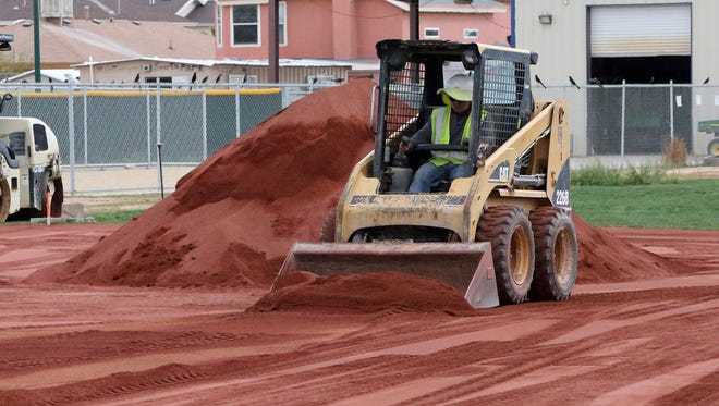 A worker spreads infield clay material onto a baseball field at the El Paso County Sportspark at 1780 N. Zaragoza. The trial between the County of El Paso and the former Sportspark's contractor and architect has been postponed until Aug. 9.