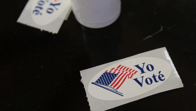 """Spanish """"I Voted"""" stickers are set out at a polling place."""