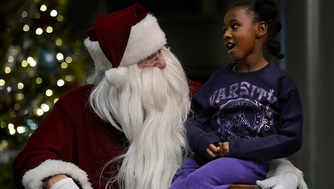 Chassidy Mcbeath, 7, of Green Bay tells Santa what she wants for Christmas during the annual Festival of Lights on Saturday at Lambeau Field.