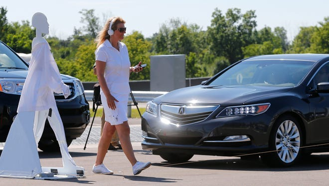 A pedestrian crosses in front of a vehicle as part of a demonstration at Mcity on its opening day in July 2015 on the University of Michigan campus in Ann Arbor. It is a 32-acre simulated city. Such technology could get a boost through the new Smart Belt Coalition.