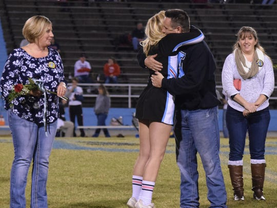 Alix Fuqua, a three year member of the UCHS cheer team gives her father, Jeff Fuqua a hug as her mother, Stacy Fuqua watches proudly.
