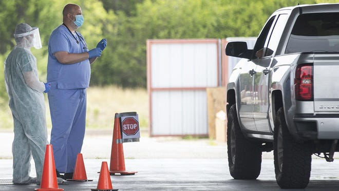 Health care workers greet a patient before administering a COVID-19 test at a Family Emergency Room drive-thru testing site in Cedar Park on Monday. People in Williamson County who have symptoms of the coronavirus or think they may have been exposed to it can schedule a drive-thru test online.