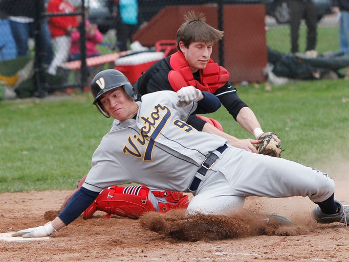 Victor's John Clemons, left, is tagged out at home by Penfield catcher Charlie Andres during a game between the Penfield Patriots and the Victor Blue Devils in Penfield on April 25, 2014.