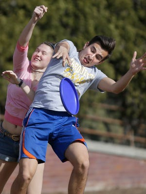 Ryan Serfas, a 20-year-old Marquette sophomore from St. Louis, battles for a Frisbee with Steph Wissing, a 20-year-old Marquette sophomore from Brookfield, as the two took advantage of the nice weather outside the Alumni Memorial Union on campus Wednesday.