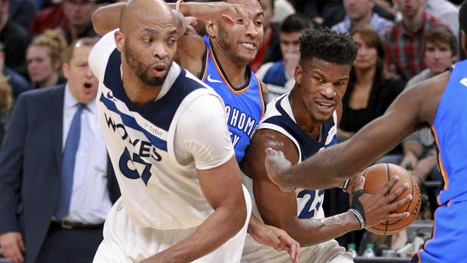 Minnesota Timberwolves guard Jimmy Butler (23) tries to squeeze past Oklahoma City Thunder Josh Huestis on a screen set by Timberwolves center Taj Gibson, left, during the first quarter of an NBA basketball game Wednesday, Jan. 10, 2018, in Minneapolis. (AP Photo/Andy Clayton-King)