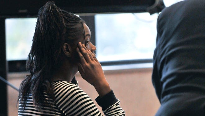 Charlisa Wood peeks at the jury during her trial Thursday in Circuit Judge Cynthia Lane's courtroom. Wood is charged with first-degree child abuse, torture and assault with intent to do great bodily harm less than murder.
