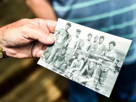 John Russell holds a photograph of him and fellow soldiers, including Frank Stump, taken in Vietnam.