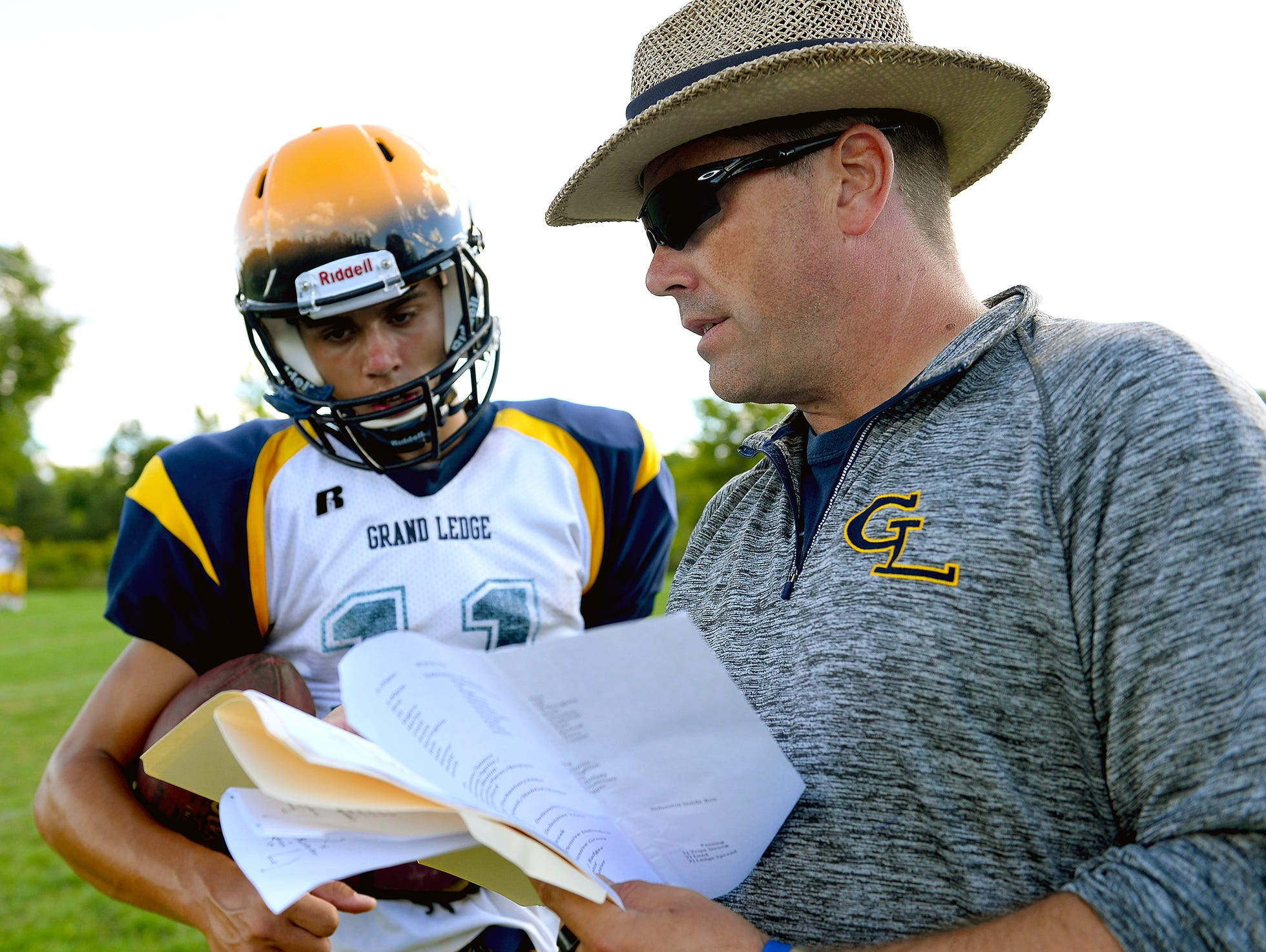 Grand Ledge quarterback back Nolan Bird and his father, and head coach Matt Bird, go over passing routes and plays during position drills at practice Monday. Nolan is entering his second season as his father's starting quarterback.