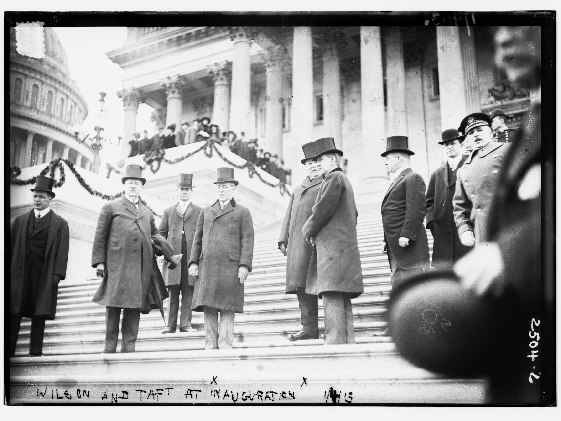 Photo shows incoming president Woodrow Wilson (center) and outgoing president William Howard Taft on the steps of the United States Capitol in Washington, D.C., at Wilson's inauguration.