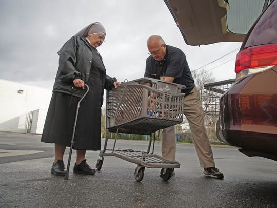 Sister Rose Marie Kietter, with Little Sisters of the Poor, and driver Dan Roberts load a cart full of donated food from ShopRite into the van they use to pick up food from various food establishments to bring back to feed residents.