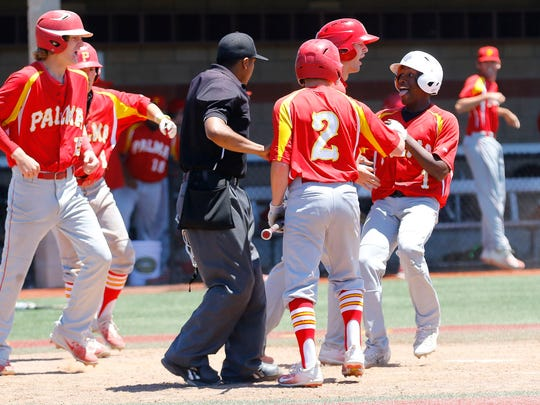 Palma's John Berring celebrates with his teammates on his way to home plate on a three-run single hit by Jacob Fajnor.