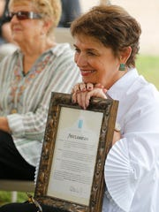 Mauren Ponce Singleton, smiles as she holds the proclamation
