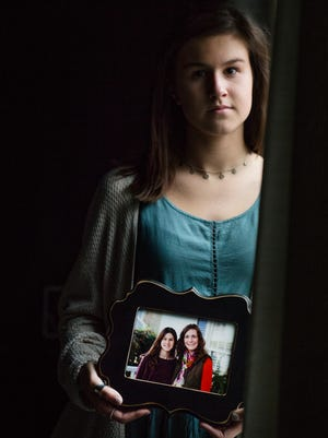 Bladen Bates holds a photograph of her and her sister, Lindsey Bates Motley, at her home on Thursday, January 11, 2018. The photograph was taken shortly before Lindsey was diagnosed with advanced colon cancer at age 26.