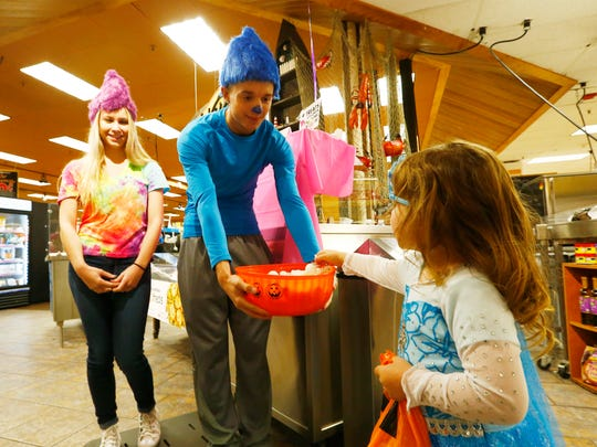 Arianna Arraign of Windsor picks a treat from, from left, Morgan Kittle an Thomas Corey during Wegmans' Halloween Parade in Johnson City on Tuesday October 24, 2017.