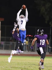 Bakersfield Christian's Jerimiah Foster (7) leaps over Mission Oak's Davin Campbell (2) for a 35 yd gain in a non-league high school football game at Bob Mathias Stadium on Sept 9th, 2016