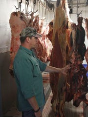 Three Suns Ranch owner Keith Mann in a cooler full of hog, bison and beef Thursday, December 11.