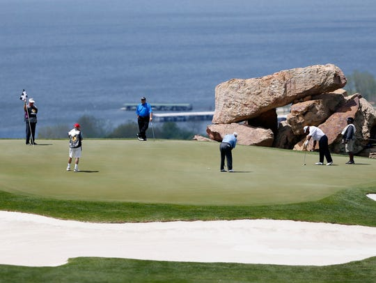 Doug Tewell putts on the 18th hole during the first