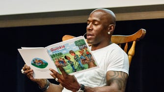 Super Bowl Champion, Donald Driver, reads his children's book to Pewaukee Lake Elementary School students during an assembly at Pewaukee High School on Monday, May 21, 2018. The students won a visit from the former Green Bay Packers wide receiver by donating 65,909 items to Goodwill during the Pack'er Up Donation Challenge in April.