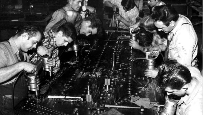 Workers assemble an aircraft panel using Milwaukee Electric Tool's hole shooters, the first lightweight, portable electric drills.
