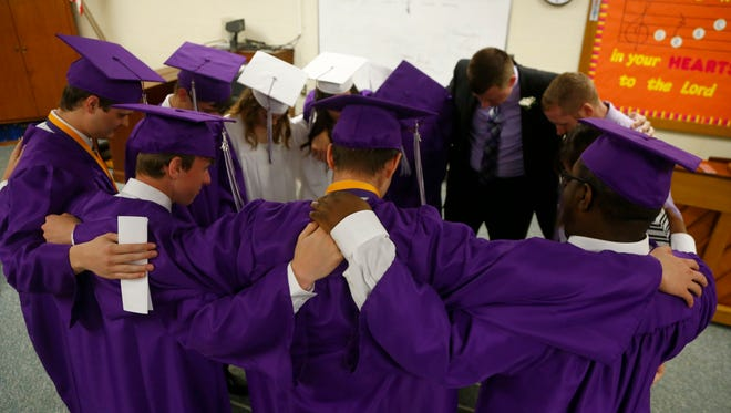 The graduating senior class from Temple Christian School prays with Principal Paul Baird before the start of commencement ceremonies on Saturday night.