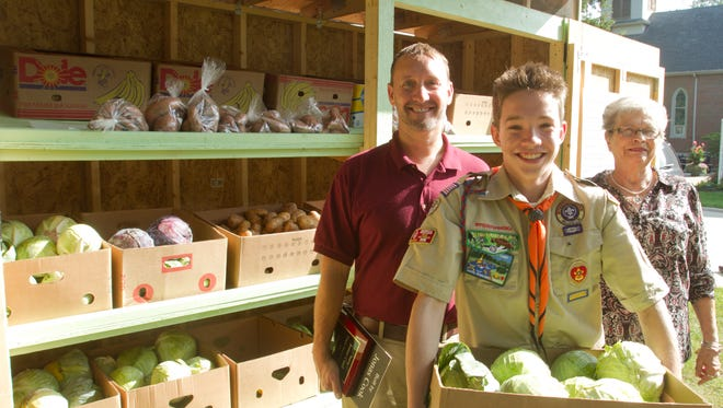 15-year-old Jonas Cook, center, poses with his father Bill and Bountiful Harvest founder and president Yvonne Cavalli Wednesday, Aug. 30, 2017 in front of the produce stand Jonas designed for his Eagle Scout project.