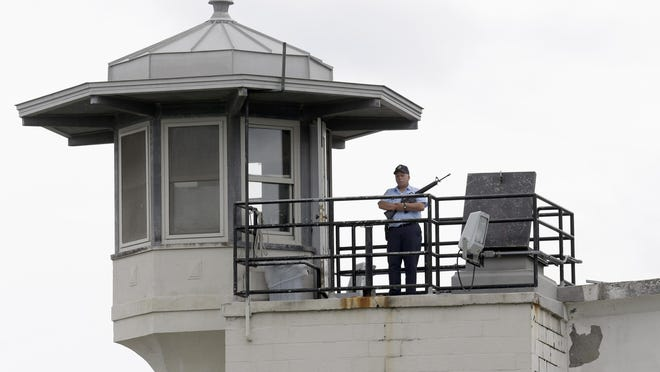 A prison employee stands guard on a tower at the Clinton Correctional Facility in Dannemora.