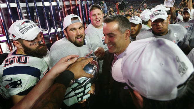 Super Bowl winning quarterback Kurt Warner carries the Vince Lombardi Trophy to the stage before it is presented to the New England Patriots, winners of Super Bowl XLIX, on Sunday in Glendale, Arizona.