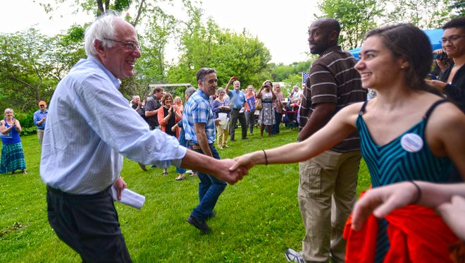 Sen. Bernie Sanders, I-Vt., greets the crowd as he enters a house party in West Branch, Iowa, where more than 175 people gathered to listen on Friday night.