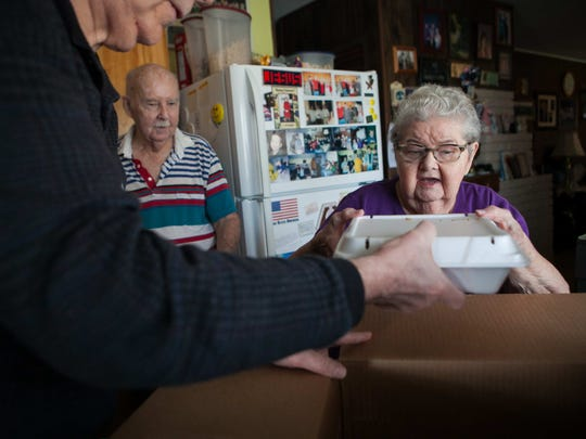"""I think it's wonderful"", says Peggy Sherwood while her husband Neil looks on as volunteer Ed Palsgrove (left) delivers Thankgiving meals to the couple."