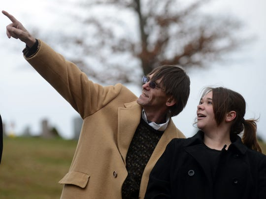 Jeff Barnes, let, points to a balloon floating away as he talks to his daughter Katie Barnes Nov. 13, 2014, at a graveside memorial service for his nephew Josh Barnes at Maple Grove Cemetery in Lancaster.