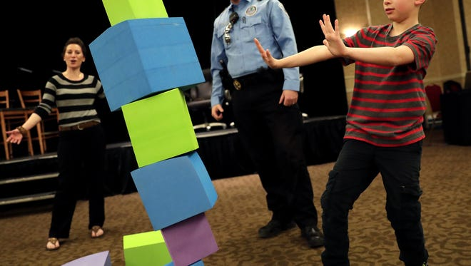 Kaukauna's Katie Connell, the community outreach director at Q90FM, reacts as her son Patrick, 9, slowly walks away from his stack of blocks while playing a game of Wonky with Matt Fillebrown, lead community service officer with the city of Appleton, during Q-Munity Game Night at the Radisson Paper Valley Hotel in Appleton on March 28.
