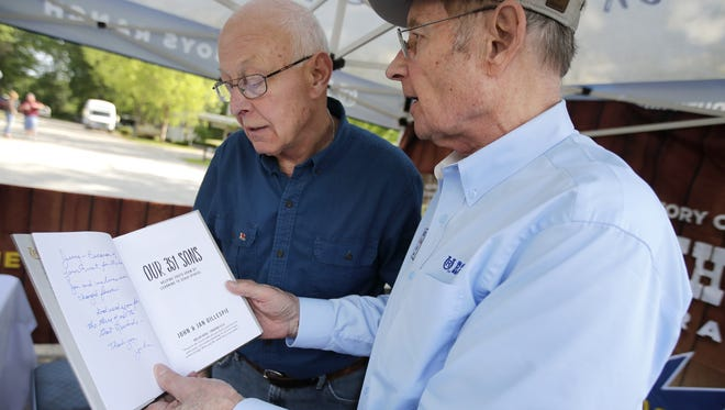 """John Gillespie, right, founder of Rawhide Boys Ranch near New London, reads the note he wrote to Jerry Monson, the first Rawhide boy, in Gillespie's book """"Our 351 Sons."""""""