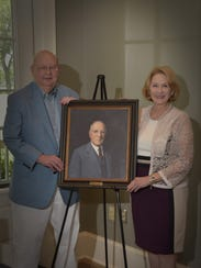 Jay and Jan  Querbes with portrait of Jay's great-grandfather,